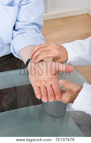 Doctor Taking Senior Man's Pulse