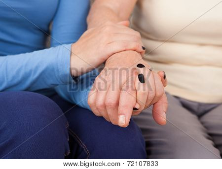 Female Caregiver Consoling Senior Woman