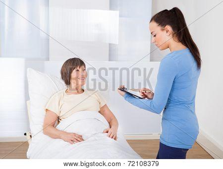 Caretaker With Clipboard Attending Senior Woman