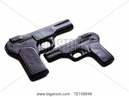 Two pistols made of dark chocolate, close-up