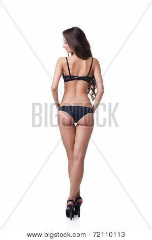 Rear view of suntanned girl in black lingerie