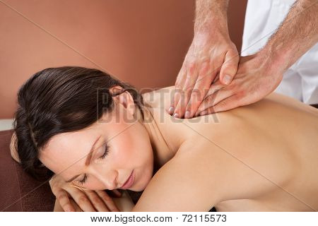 Woman Receiving Back Massaging In Spa