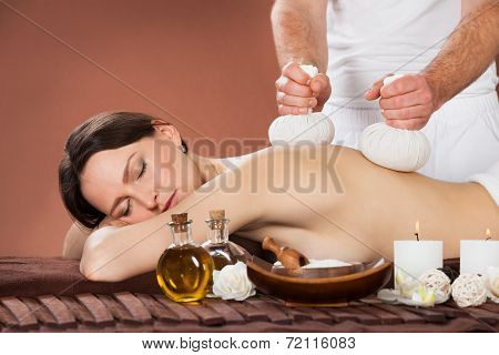 Woman Receiving Massage With Herbal Compress Stamps At Spa