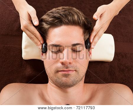 Handsome Man Receiving Hot Stone Therapy In Spa