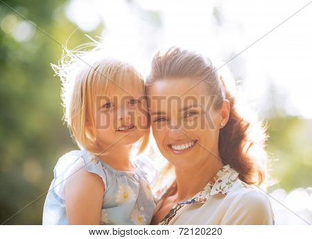 Portrait Of Happy Mother And Baby Girl Outdoors In Park