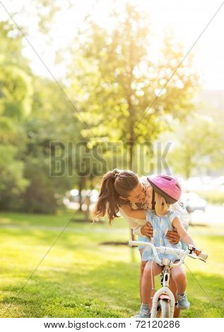 Mother Helping Baby Girl Riding Bicycle Outdoors