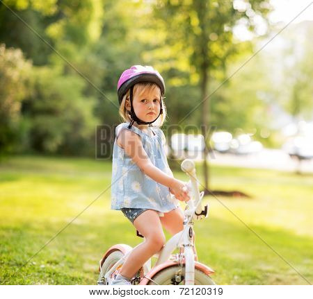 Portrait Of Displeased Baby Girl With Bicycle In Park