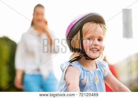 Portrait Of Smiling Baby Girl Riding Bicycle