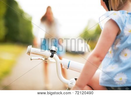 Closeup On Baby Girl Sitting On Bicycle And Mother Waiting In Ba