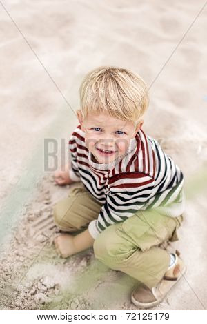 Beautiful blonde boy playing with sand on the beach