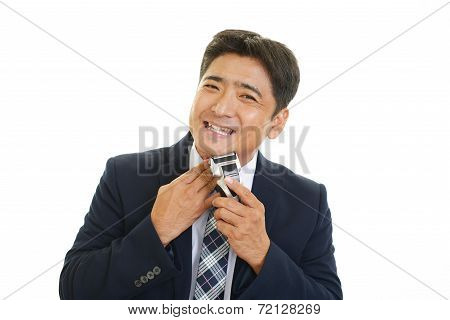 A man shaving with electric razor