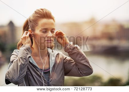Portrait Of Fitness Young Woman Wearing Earphones In City In The