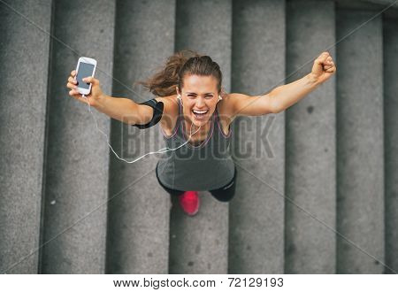 Portrait Of Happy Fitness Young Woman With Cell Phone Outdoors I