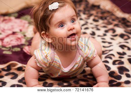 Baby Lying On A Rug.