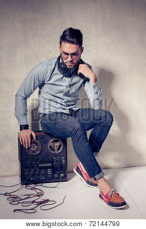 Handsome Man Listening To Music On A Magnetophone Against Grunge Wall