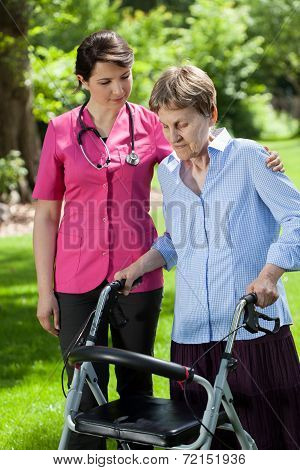 Physiotherapist Looking At Woman Using Orthopedic Walker