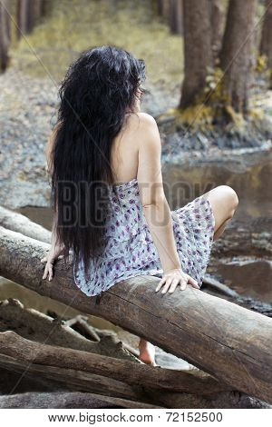 Girl Sitting On A Log In The Forest