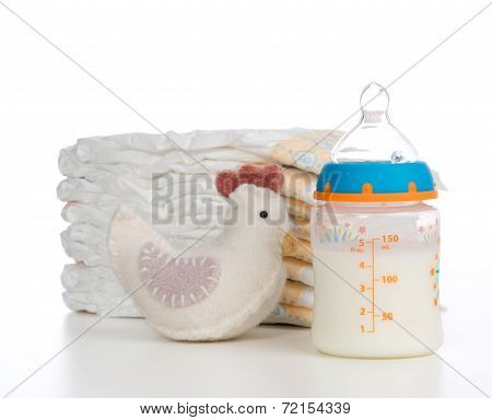 New Born Child Composition Stack Of Diapers Toy And Baby Feeding Bottle