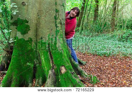 Man Looking Around A Tree