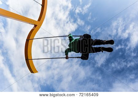 Silhouette Of A Boy Swinging On A Swing