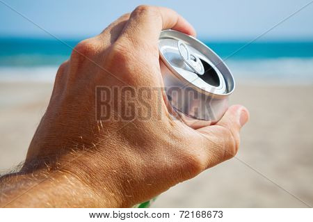 Aluminum Can Of Beer In A Male Hand With Beach And Sea On Background