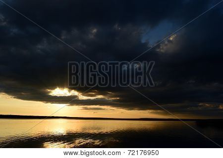 The Cloud Hid The Sun Over The Lake At Sunset, The Sun's Rays Broke Through The Cloud In The Sky