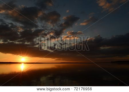 Sunset Clouds Over The Water Of The Lake The Sun's Rays Are Reflected In The Mirrored Surface Of The