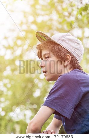 Profile Of A Young Boy With Base Cap And Blurred Green Leafs In Background