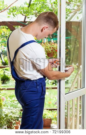 Handyman Adjusting A Window Handle