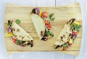 stock photo of portobello mushroom  - Tacos filled with roasted portobello mushrooms zucchini and purple onions with cherry tomatoes cilantro and monterrey jack cheese - JPG