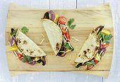 image of portobello mushroom  - Tacos filled with roasted portobello mushrooms zucchini and purple onions with cherry tomatoes cilantro and monterrey jack cheese - JPG
