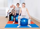 picture of senior class  - Portrait of smiling trainer and senior customers sitting on fitness balls in exercise class - JPG
