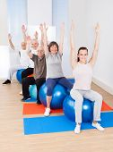 image of senior class  - Full length portrait of trainer and senior customers stretching on fitness balls in exercise class - JPG