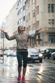 foto of rain-drop  - Full length portrait of happy fitness young woman catching rain drops in the city - JPG