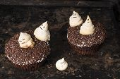 stock photo of funny ghost  - Chocolate pumpkin cupcake decorated with meringue ghosts - JPG