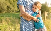 stock photo of grandmother  - Portrait of happy grandson hugging grandmother over a nature outdoor background - JPG