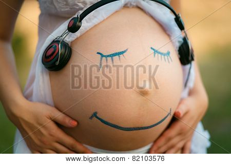 Pregnant Woman Belly Closeup With Smiling Funny Face Drawing On It, Listening To The Music In Earpho