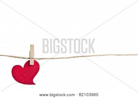 Red Fabric Heart Hanging On The Clothesline . On White Background
