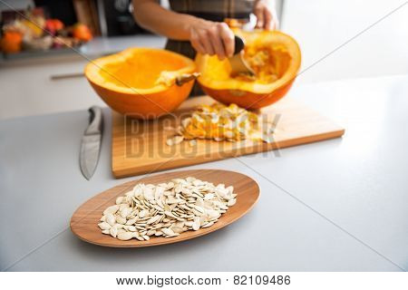 Closeup On Seeds And Young Housewife Removing Filling From Pumpkin In Background