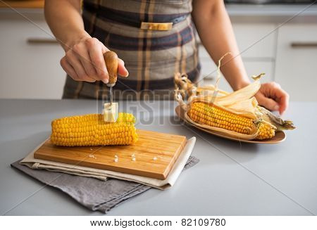 Closeup On Young Housewife Rubbing Boiled Corn With Butter