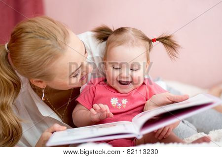 happy mother read a book to child girl