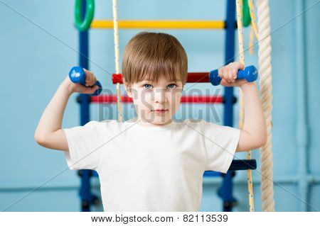 Strong kid boy exercising with dumbbells