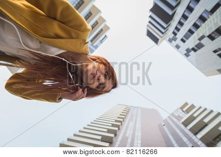 Redhead Girl Listening To Music In The City Streets