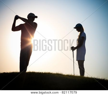 Male And Female Golfers Playing Golf