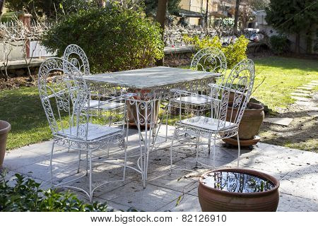 Decorative vintage metal white table and chairs furniture in a garden