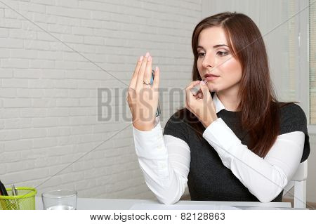 Girl Applies Lipstick Looking At The Phone
