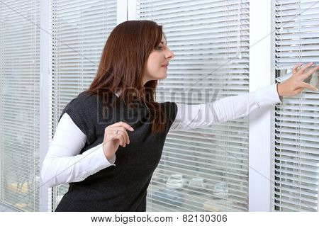Girl Peeking Through Window Blinds On The Street