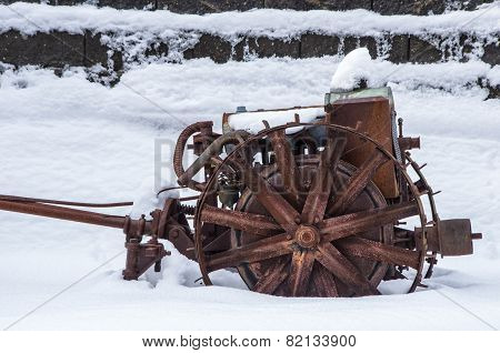 Rusted Farm Equipment In Snow