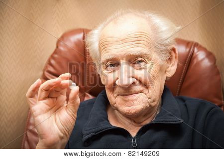 Old Smiling Man Holding A Pill