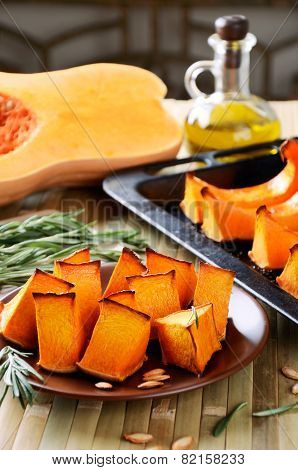 Orange Baked Pumpkin, Rosemary And Olive Oil On A Kitchen Table Vertical